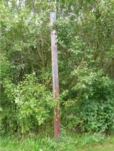 Ein Holzbalken/Stamm, der aufrecht zwischen Büschen am Rand einer Grasfläche im Boden steht, etwa 3m hoch. Er ist mit einigen fast senkrechten Linien und kleinen bunten Quadraten auf dunkelrot/lilanem Hintergrund bemalt.